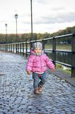 Little girl walks along the waterfront. In the autumn afternoon Stock Photos