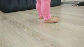 Little girl walks barefoot in her living room,. Feet close-up stock footage