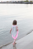 A little girl walks on the beach Stock Photos