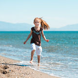 Little girl walks on the  beach Stock Image