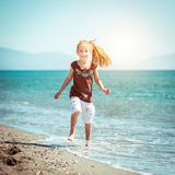 Little girl walks on the  beach Stock Images