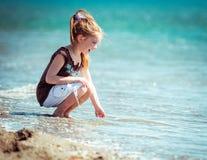 Little girl walks on the  beach Stock Photos