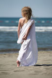 Little girl walks at the beach in white clothes. Young girl goes away, walking in sand Royalty Free Stock Photography