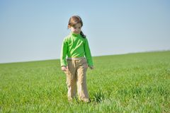 A little girl walks in a field. Stock Image