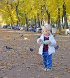 Little girl walks in gardens in fall royalty free stock photo