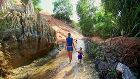 Little Girl Walks by Hand with Mother along Fairy Stream. Little girl in blue swimsuit walks by hand with mother along Fairy Stream past rocky steep bank in stock video footage