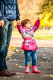 Little girl walks with my dad. Pointing to something in the park Stock Image