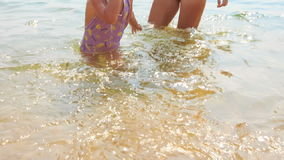 Little Girl Walks out of Sea against Mom in Bikini Straw Hat stock video