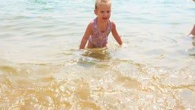 Little Girl Walks out of Sea against Mom in Bikini Straw Hat stock footage