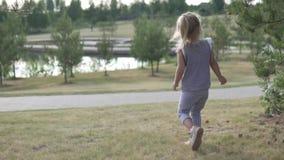 Little girl walks in the park. stock video