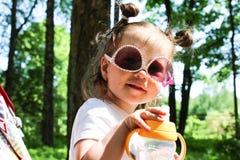 A little girl walks sitting in a pram in sunglasses. Little girl smiling in child stroller seat in car park stock images