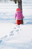 Little girl walks in snow covered winter park and looks at the t. Ree. Deep footprints in the snow. Blind alley royalty free stock images