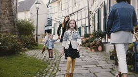 Little girl walks to camera, relaxed and smiling. European mother together with two kids. Half timber houses Germany 4K. Little girl walks to camera, relaxed stock video