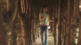 Little girl walks through the tunnel of trees. the child in the mysterious and magical forest. slow motion stock video footage