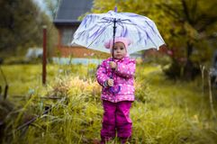 A little girl walks with an umbrella in the rain in the country. Girl walking in the rain under an umbrella stock images