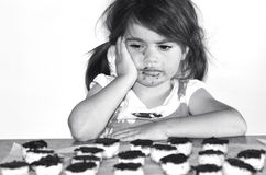 Little girl wants to eat lots of chocolate cookies Stock Images