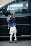 Little girl wants to open car royalty free stock photo