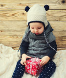 Little girl wants to open a gift box. Stock Image