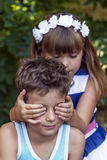 Little  girl wants to surprise the boy. First love. Little sweet boy and a girl standing by the bench in the park and having fun. The girl wants to surprise the Royalty Free Stock Image