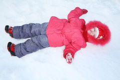 Little girl in warm clothes lies in snow Stock Image