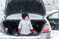 Little girl in warm clothes standing in open trunk of car in winter Royalty Free Stock Photos