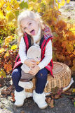 Little girl in warm clothes with toy rabbit Stock Image