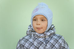 Little girl in warm coat with cap Stock Photos