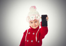 Little girl in warm hat and a red sweater shows smartphone Stock Images