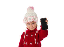 Little girl in warm hat and a red sweater shows smartphone Stock Photo