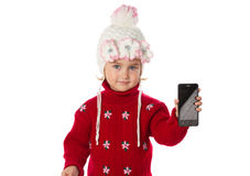 Little girl in warm hat and a red sweater shows smartphone Royalty Free Stock Images
