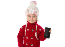 Little girl in warm hat and a red sweater shows smartphone Royalty Free Stock Image