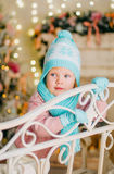 Little girl in warm knitted hat, mittens and scarf. Portrait of a pretty little girl in warm knitted hat, mittens and scarf sitting on a bench; Christmas studio royalty free stock photography