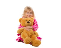 Little girl in warm pink bathrobe with Teddy bear  on a white ba Royalty Free Stock Photo