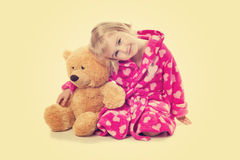 Little girl in warm pink bathrobe with Teddy bear  on a white ba Royalty Free Stock Image
