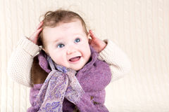 Little girl in warm purple jacket sitting on knitted blanket Stock Images