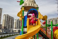 The little girl, warmly dressed, in a hat and jacket plays on the playground with slides and swings in the courtyard of residentia stock photos