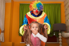 Little girl was frightened of the clown. Little girl was frightened of the clown who has crept behind. Kindergarten with colorful couch on the background Royalty Free Stock Photo