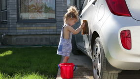 Little girl wash a car. Child helping family clean car stock video