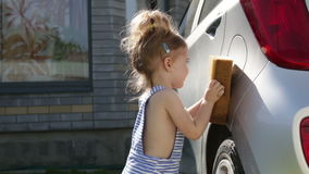 Little girl wash a car. Child helping family clean car stock footage