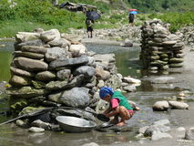 Little girl wash dishes in river - Nepal Royalty Free Stock Image