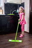 Little girl washes floor with a mop royalty free stock image