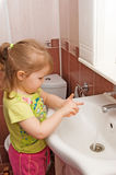 The little girl washes hands. At home Royalty Free Stock Photos