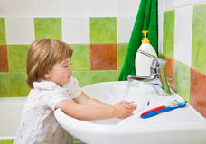 Little girl washes hands. Royalty Free Stock Photo