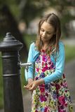 Little  girl washes hands under water hand pump on the street in the old town. Stock Images