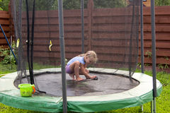 Little girl washes her trampoline in backyard Stock Photography