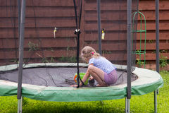 Little girl washes her trampoline in backyard Stock Image
