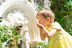 Little girl washes in a source. In green bushes Stock Photo