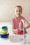 Little girl washing the dishes. Portrait of a 6 years old girl washing the dishes at home Stock Images