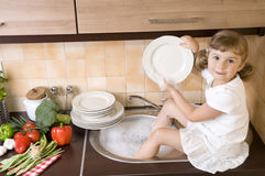 Little girl washing dishes Stock Photo
