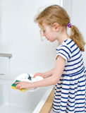 Little girl washing the dishes. Royalty Free Stock Photo